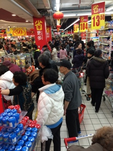 People pack out a supermarket to buy food two days before the lunar new year.